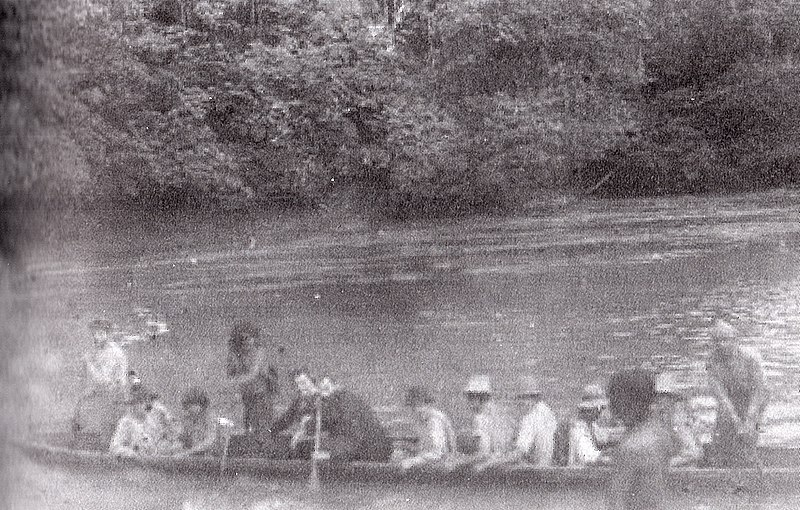 Father Carlo Crespi driving a canoe with settlers and Shuar Indians, between 1923 and 1937